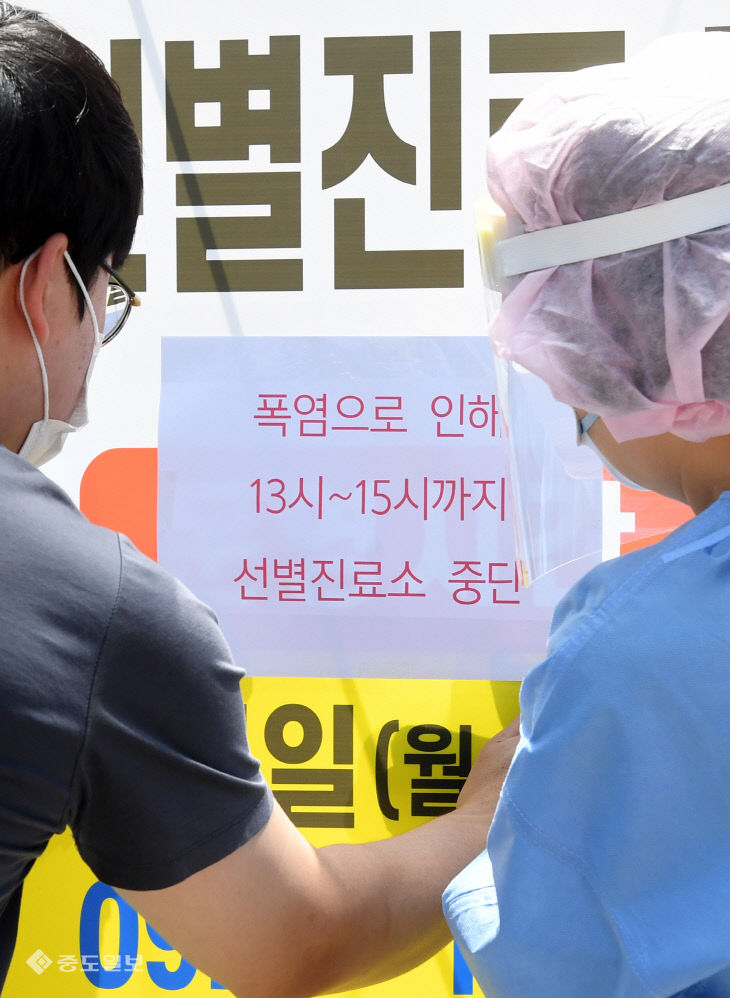 폭염으로 변경된 선별진료소 운영시간 붙이는 의료진