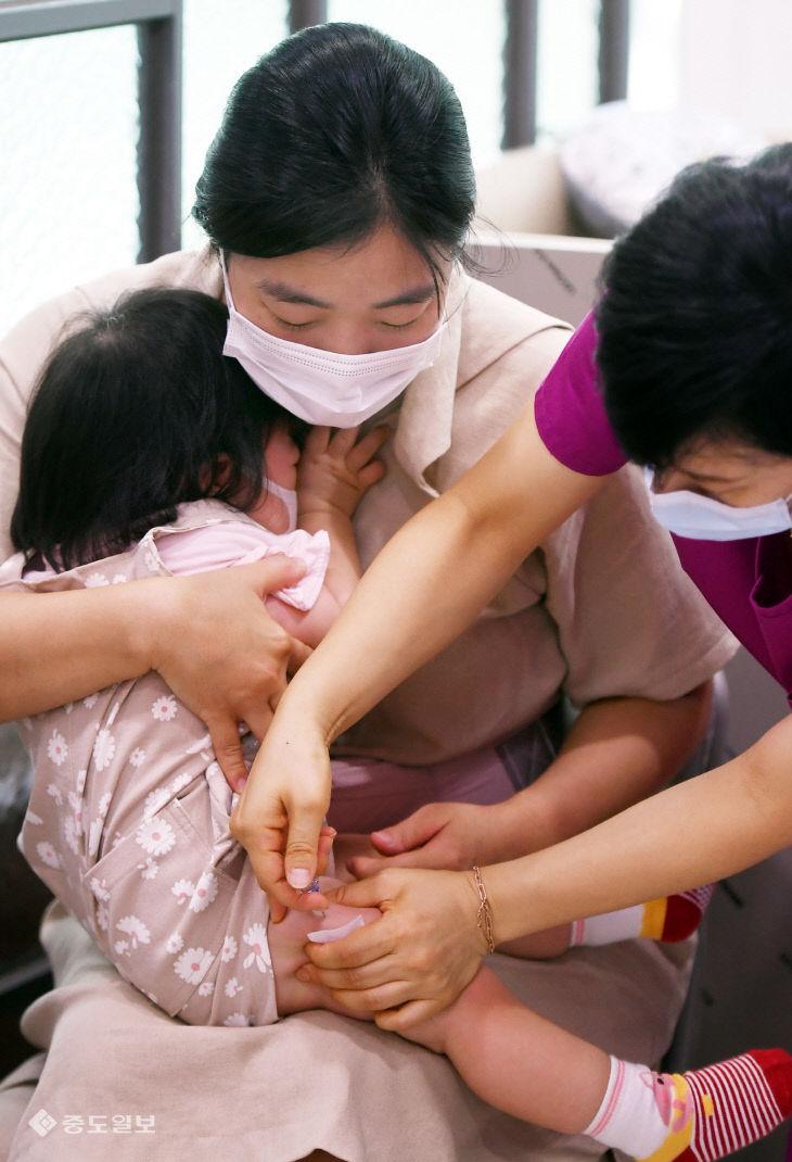 엄마 품에서 인플루엔자 국가예방접종 맞는 영아